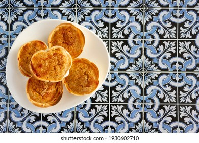 Traditional Portuguese pastry called Queijada de Sintra on portuguese tiles background. Top view with copy space