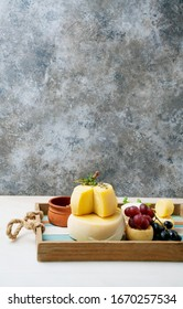 Traditional Portuguese semi-soft cheeses from evora alentejo and azores regions on the tray, served with fresh grapes, honey and herbs. Side view