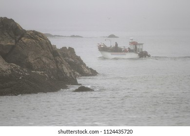 Traditional portuguese small fishing boat in the toil between boulders. Northern portuguese rocky coast in a summer foggy morning.