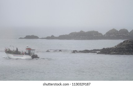 Traditional portuguese small fishing boat during toil between boulders. Northern portuguese rocky coast in a summer foggy morning.