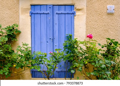 A traditional Provencal window with blue shutters, roses flowers in front of window.