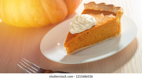 Traditional pumpkin pie preparation with filling, dough and ingredients on dark rustic background, top view, retro styled, frame