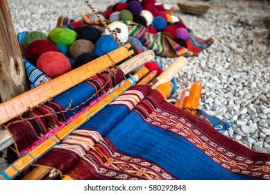Traditional Quechuan alpaca weaving tools and balls of alpaca yarn