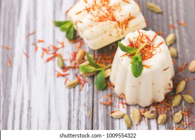 Traditional Rajasthani Indian cuisine. Homemade kulfi dessert, ice cream with safron, mint and nuts on gray wooden background. Copyspace, top view.