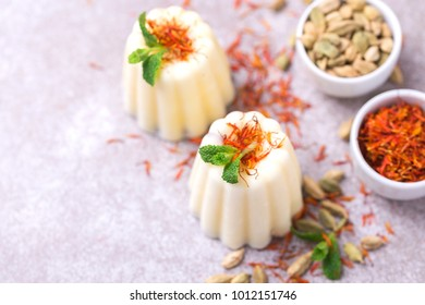 Traditional Rajasthani Indian cuisine. Homemade kulfi dessert, ice cream with safron, mint and nuts on gray slate background. Copyspace, top view.