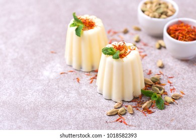 Traditional Rajasthani Indian cuisine. Homemade kulfi dessert, ice cream with safron, mint and nuts on gray slate background. Copyspace, horizontal view.