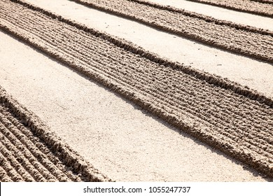 A traditional raked sand garden shows a geometric rigid pattern of alternating lines of smooth and rough surfaces.