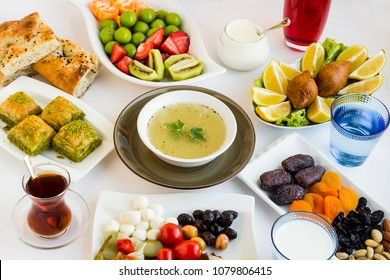 Traditional Ramadan (iftar) table with soup,baklava,pide,stuffed meatball,dry date fruits,Turkish tea,fresh fruits and black olives on the white surface.All foods designed around soup.