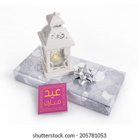 """A  traditional ramadan lamp placed on a silver gift box with """"Eid Mubarak' message in Arabic script."""