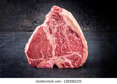 Traditional raw dry aged wagyu porterhouse steak as closeup on an old rustic board