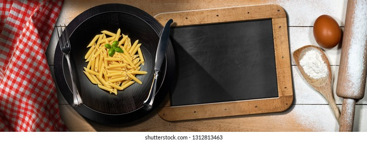 Traditional raw food called Penne or macaroni, Italian pasta in a wooden dish on a table with kitchen utensils, flour, egg and an empty blackboard with copy space