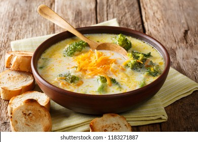 Traditional recipe of broccoli cheese soup with vegetables in a bowl with toast close-up on the table. horizontal