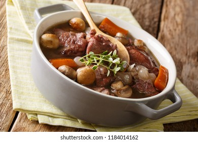 Traditional recipe of French cuisine Coq au vin close-up in a pot on the table. horizontal
