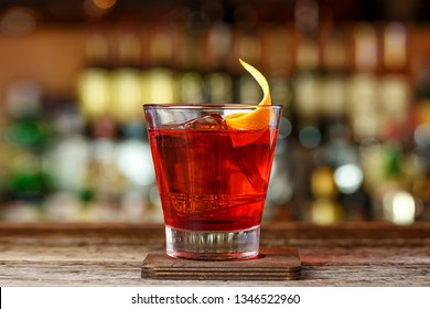 Traditional recipe Negroni - gin, campari and martini rosso. The cocktail stands on the blurred background of the bar
