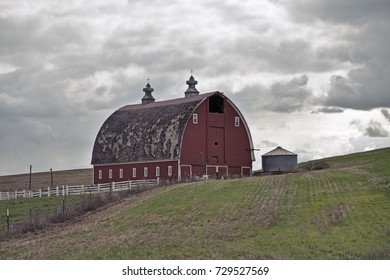 A traditional red barn on a farm stands on one of the rolling hills in the Palouse area of Eastern Washington.