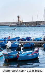 Traditional red and blue fishing boats in Monopoli port near Castle of Carlo V, Apulia, Bari province, Italy