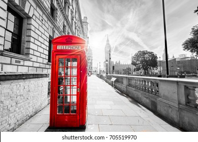 Traditional red British telephone box in London with sunlight