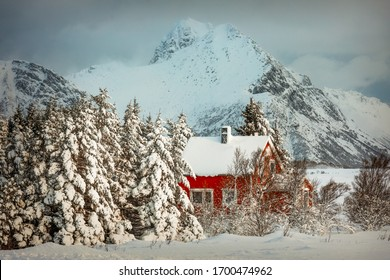 Traditional red cabin under heavy snow in winter, somewhere in Lofoten islands, Norway, with a hint for Christmas and Santa Claus