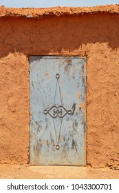 Traditional red earth wall with metal door in Morocco, Ait Ben Haddou, World Heritage site