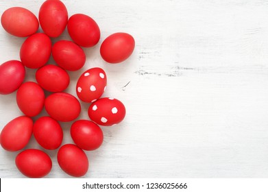 Traditional red Easter eggs on white shabby wooden table. Top view point.