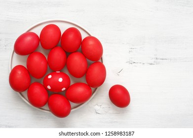 Traditional red Easter eggs in plate on white shabby wooden table. Top view point.