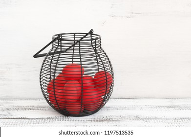 Traditional red Easter eggs in wire basket on shabby wood table against vintage white background.