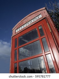 TRADITIONAL RED ENGLISH TELEPHONE KIOSK WITH BLUE SKY