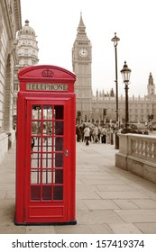A traditional red phone booth in London with the Big Ben in a sepia background, short focus, background is blurred.