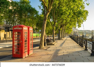 A traditional red phone booth in London at sunny morning