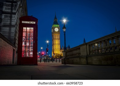 Traditional red phone booth or telephone box at night with Big Ben in the background, the famous english landmark in London, England, UK
