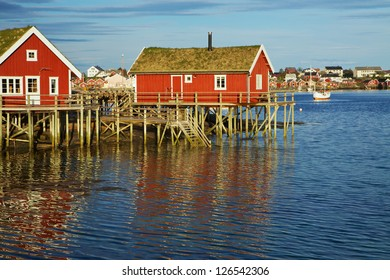 Traditional red rorbu huts with green roofs in fishing town of Reine on Lofoten islands in Norway