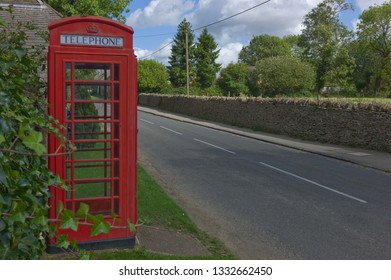 A traditional red telephone along a road in the UK with trees and clouds. Space for text at the right side