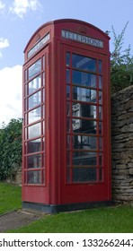 A traditional red telephone box against a stone wall