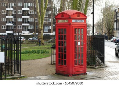 A traditional red telephone box in beside a park in Bloomsbury, London, England