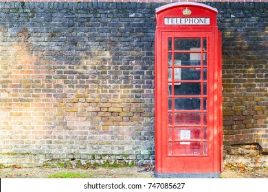 Traditional red telephone box on street of Hampstead Heath in London against a grungy brick wall