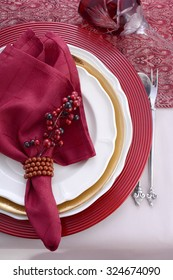 Traditional red theme festive table place setting for Christmas or Thanksgiving dinner party table.
