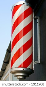 A traditional red and white striped barber's pole.