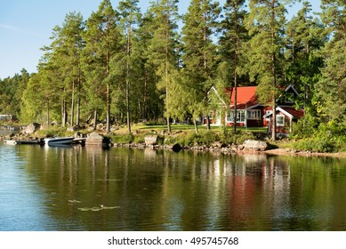 Traditional, red wooden house on a lake in Smaland, Sweden, in an early summer morning