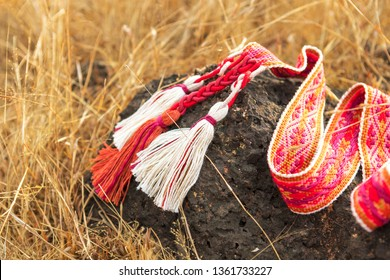 Traditional red woven Slavic belt on black stone in dry yellow grass.