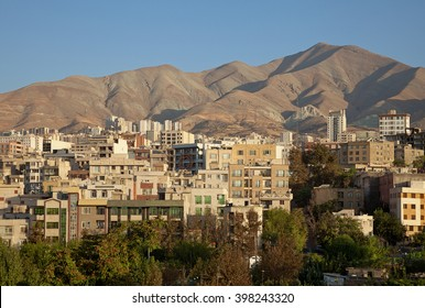 Traditional residential buildings in the skyline of Tehran between brown hills  and a row of greeneries on a clear sunny day.