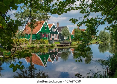 Traditional residential Dutch buildings, reflected in the water. In Zaandam, the windmill village