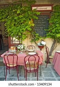 Traditional restaurant exterior with tables, chairs and menu, France