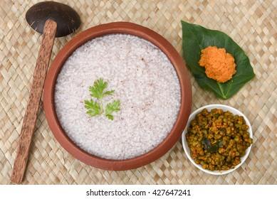 Traditional rice porridge/ payaru kanji  / congee / rice soup, whole green gram curry with coconut / tomato chutney in Kerala, India. Indian food in earthen ware / mud / clay pot