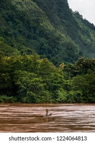 Traditional River Skiff Canoe on Wide Laotian River with View of Dense Jungle Vegetation on Mountain Side. Portrait Orientation. (Nam Ou River, Muang Ngoi, Laos).