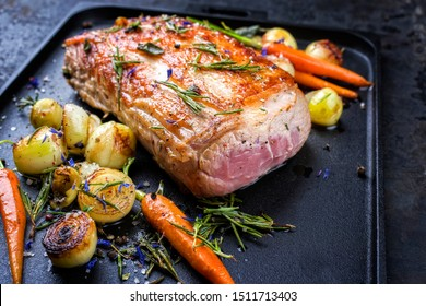 Traditional roasted dry aged veal tenderloin with carrots and onions offered as closeup on a modern design cast ion tray