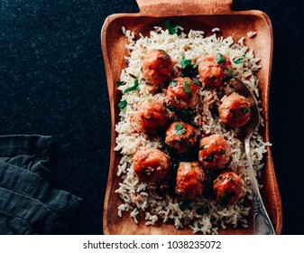 Traditional roasted meatballs with rice and tomato sauce on a wooden plate.