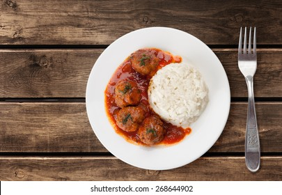Traditional roasted meatballs with rice and tomato sauce