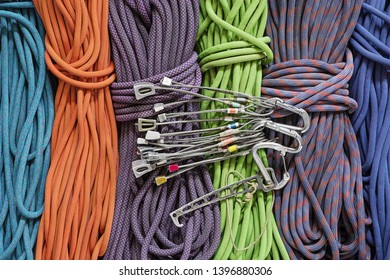 traditional rock climbing protection with used stoppers and nut tool and carabiners over a background of climbing ropes