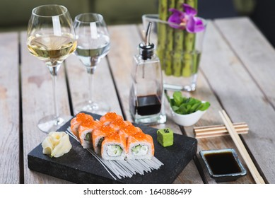 Traditional roll with red fish on a stone board with wine, sauces, vasabi on a table in a restaurant. Japanese food. Seafood on the table in a restaurant. Beautiful serving and creative decoration.