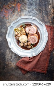 Traditional rolled boar roast with bread dumpling, fried chicory and mushroom as top view on a pewter plate in game red wine sauce with copy space